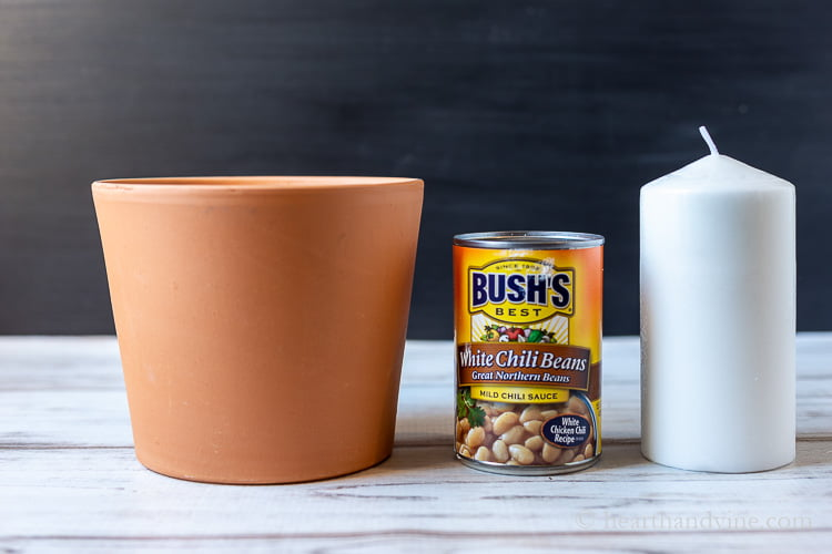 Clay pot, can of chili beans and a white pillar candle.