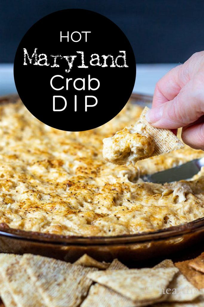 A hand holding a cracker with Maryland crab dip above a pan of the dip.
