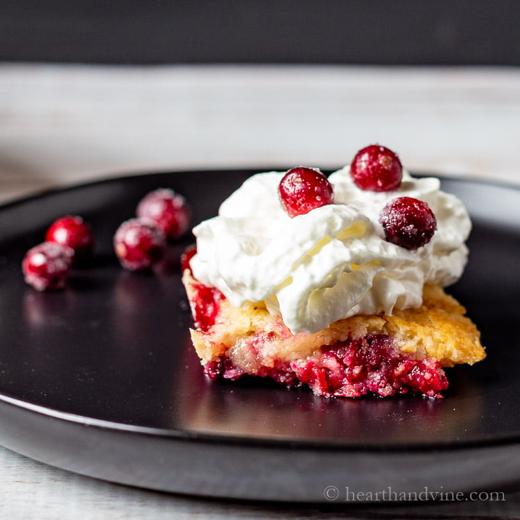 A slice of homemade cranberry dump cake topped with cream and more sugared cranberries.