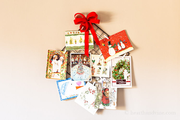 Christmas card hanging holder with red bow and mini clothespins fill with Christmas cards.