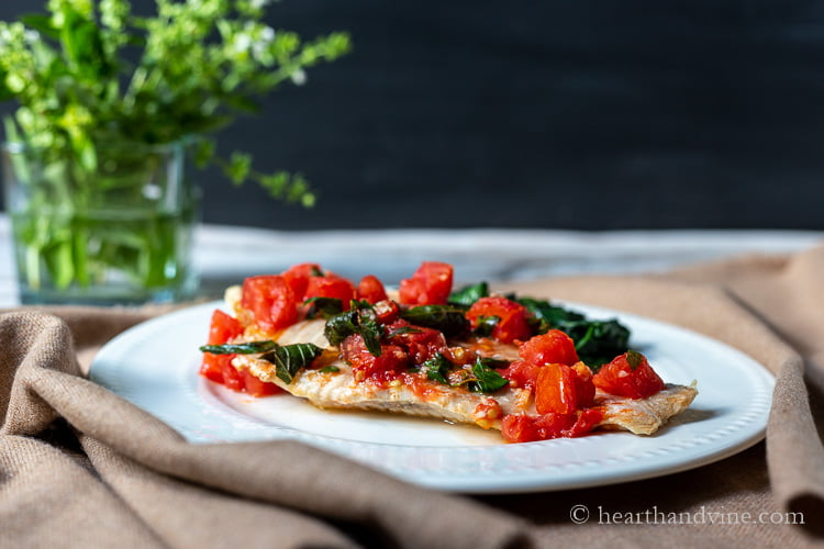 Large white fish filet with tomatoes and basil on top next to sautéed spinach on a dinner plate.