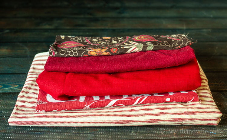Five folds of fabric in shades of red. Two solid and three patterned.