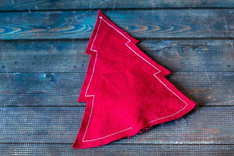 Sewn dark red fabric in a tree shape with white stitching.