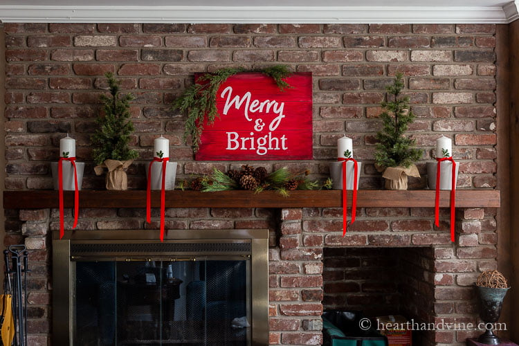 Full view of a fireplace mantel decorations with a red and white sign that says Merry & Bright above pine and pine cones. Gray painted clay pots with white pillar candles wrapped with red velvet ribbon and a sprig of box wood in the ribbon. Two small faux evergreen trees are on the side with burlap bases.