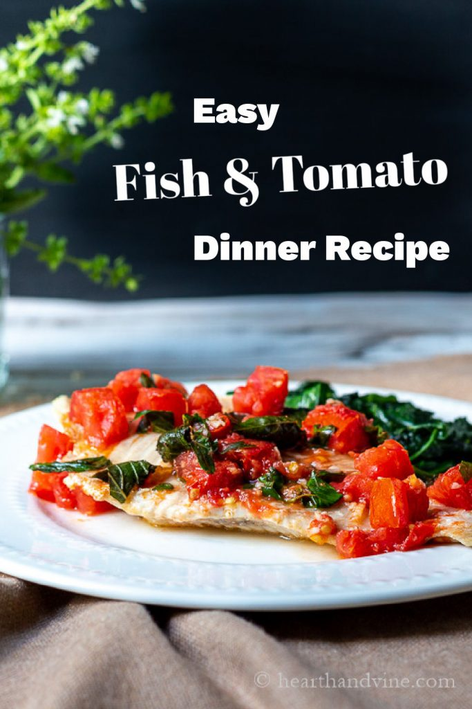 Large white fish filet with tomatoes and basil on top next to sautéed spinach.
