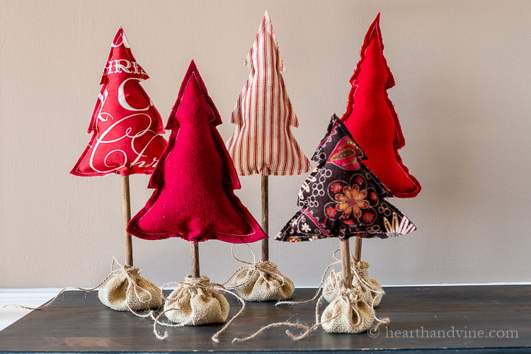 Five different heights of fabric trees in shades of red. Two solid, one striped and two patterns.