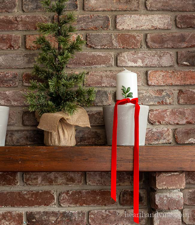 A small faux tree with a wrapped burlap base next to a gray painted pot with a white pillar candle. The candle is has a red velvet ribbon with a sprig of boxwood tucked in at the knot.