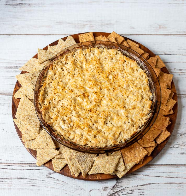 Crab dip in a dark round glass pan with small square crackers on one side and triangle crackers on the other side.