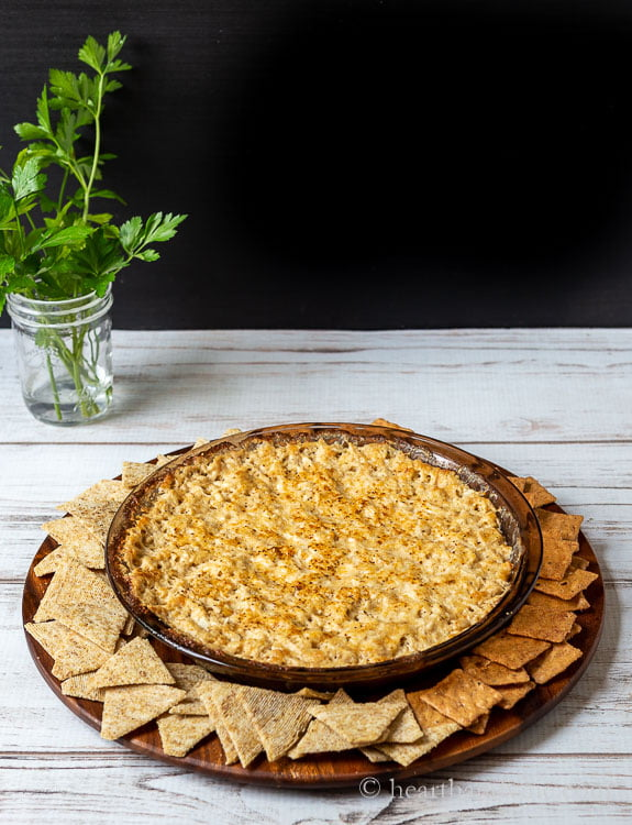 Baked Maryland crab dip baked in an amber glass pie pan on a wood serving plate with triscuits and small square crackers.