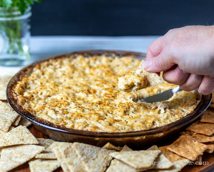 A hand holding a cracker with Maryland crab dip above a pan of the same dip surrounded by crackers.