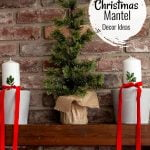Fireplace mantel with gray clay pots, white candles, red ribbon and small faux trees.