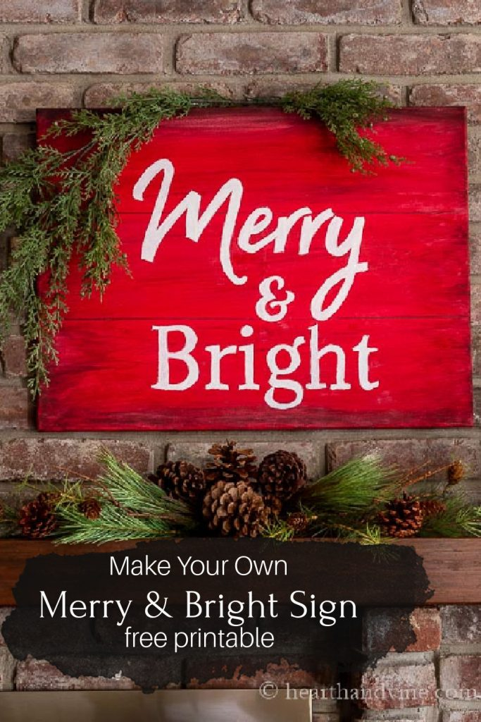 A red and white sign saying Merry & Bright hung about a wood mantel with greenery and pine cones.