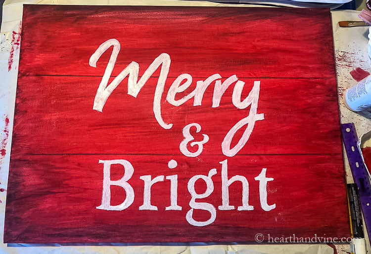 Merry and Bright in white chalk paint on a red canvas.