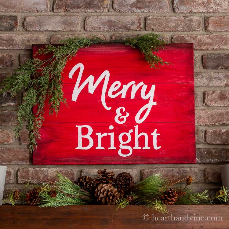 """Decorated DIY Christmas sign on a decorated fireplace mantle. It's a large red sign with white letters saying, """"Merry & Bright"""" above greens and pinecones."""
