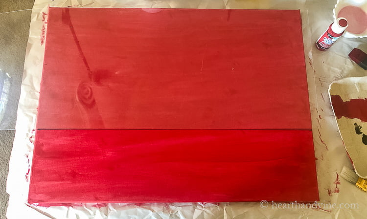 A red painted canvas in a landscape view with a piece of plexiglass lying on top cover 2/3 of the top and a dark line drawn at the bottom.
