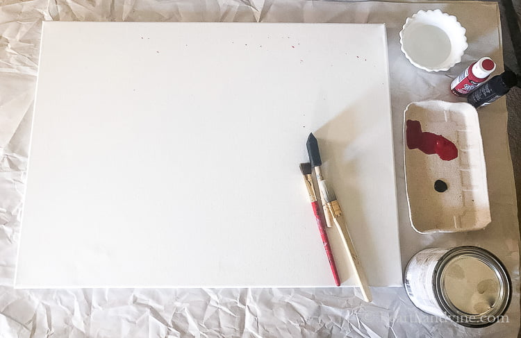 A plain white canvas, paint brushes, water in a bowl, a plate with red and black paint and a small paint can.