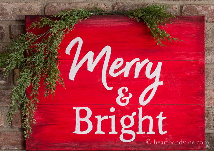 Red and white Merry & Bright DIY Christmas sign with artificial cedar hanging on the upper left corner.