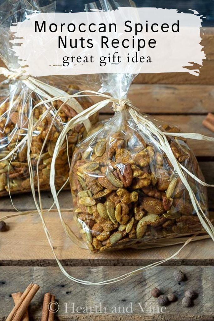 Two bags of Moroccan spiced nuts on a  crate with cinnamon sticks and allspice.