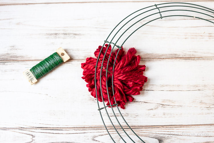 Green wire paddle and green wire wreath frame with a red pom pom tied on with green wire in the back.