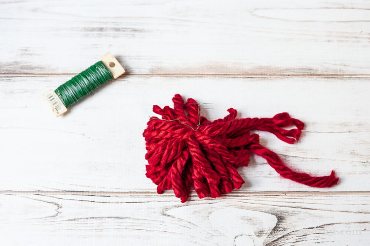 Green floral wire paddle and a loose red pom pom with wire in the middle.