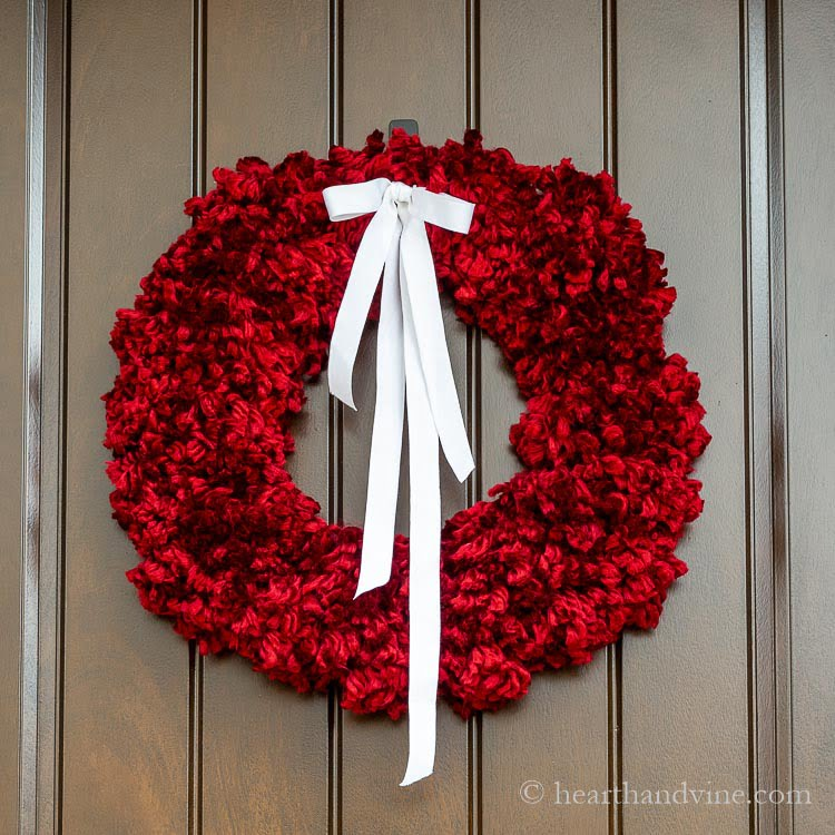 Red chunky yarn pom pom wreath on brown door with a white ribbon.