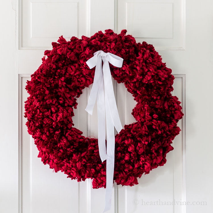 Red yarn pom pom wreath on white door.