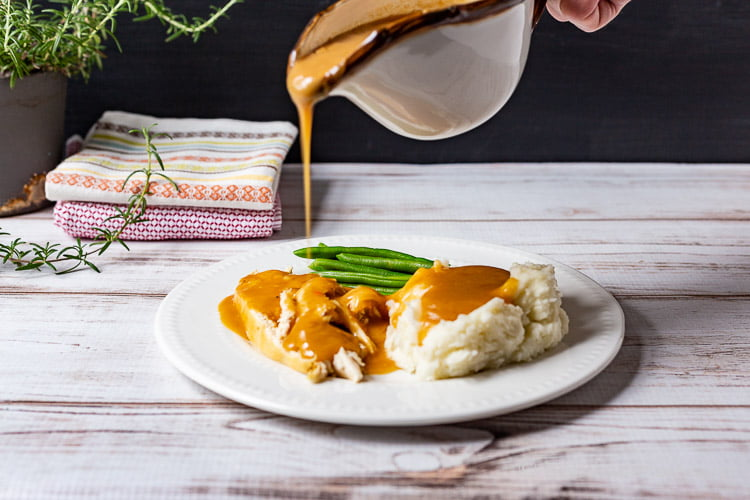 Plate of green beans, chicken and mashed potatoes. Above a gravy boat is pouring gravy onto the chicken.