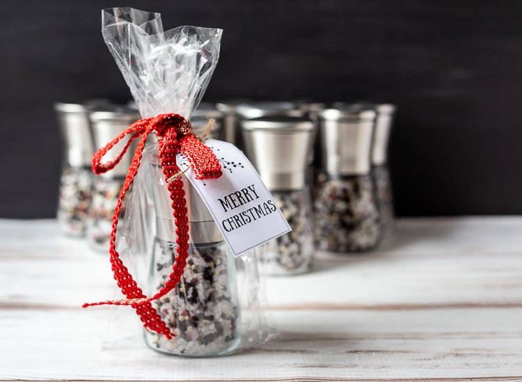 A salt and pepper grinder gift wrapped in a cellophane bag with a red ribbon and a Merry Christmas tag.