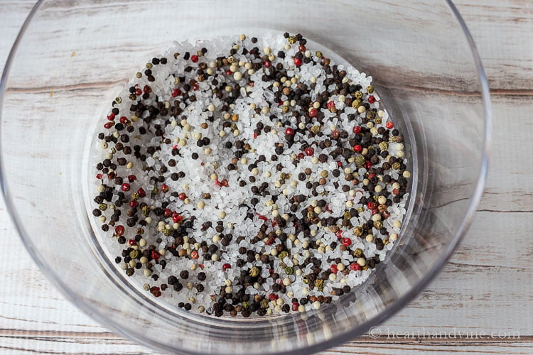 A  large clear bowl filled with some coarse salt and rainbow peppercorns.