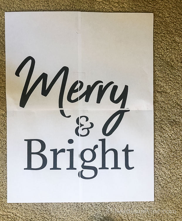 Four pieces of computer paper with the words Merry & Bright spelled out and taped together.