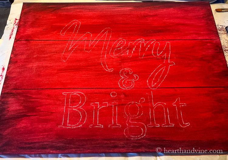A red painted canvas with the words Merry & Bright traced on top.