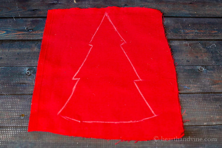 Outline of tree on red fabric.