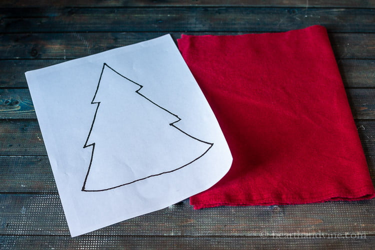 Paper with a tree drawing and a piece of dark red flannel fabric.