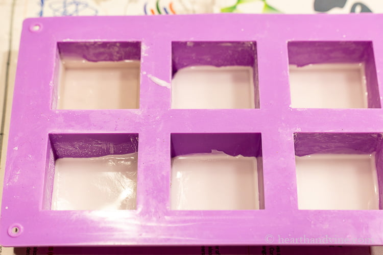 Six cell square soap mold with a small amount of beeswax in each cell.