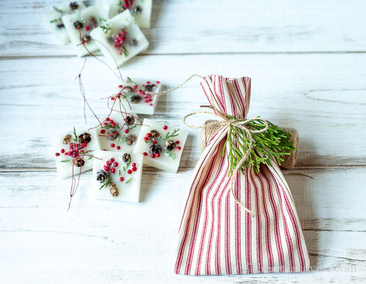 Christmas wax scented ornament in a small pile next to a red and white striped fabric bag with a twine ribbon and some fresh greenery.