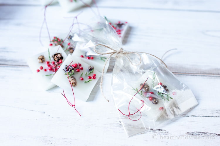 Several square wax Christmas ornaments next to one in wrapped up in a cellophane bag with a jute ribbon.