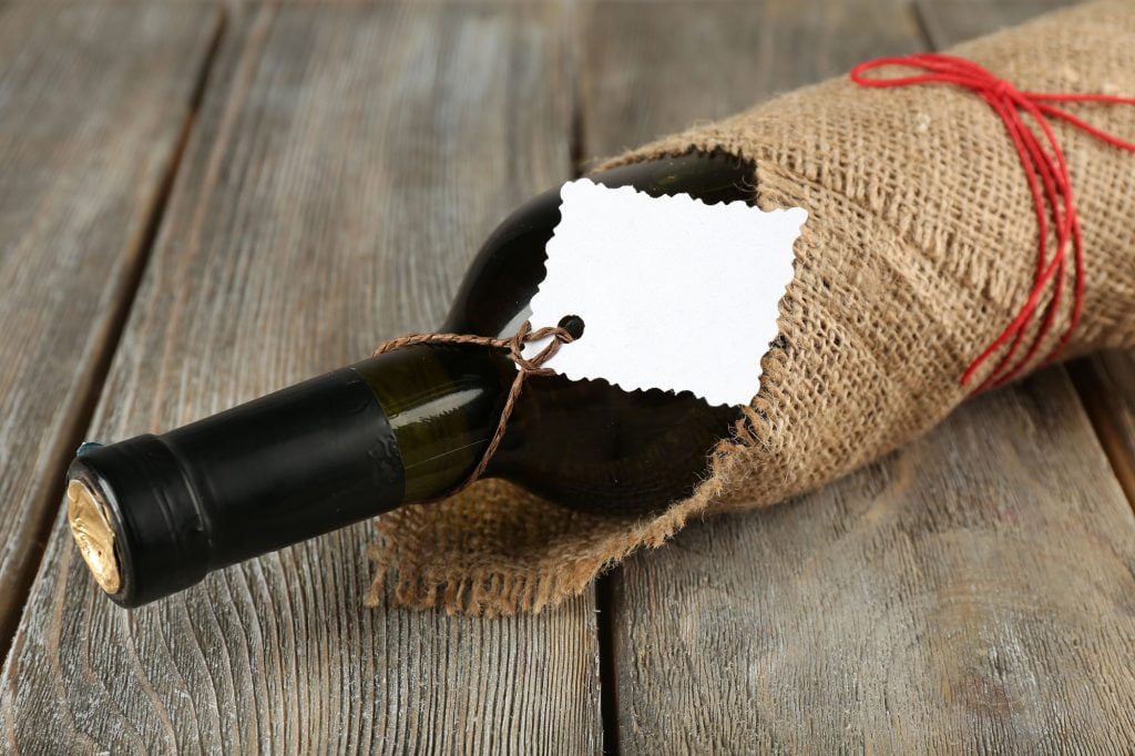 Wine bottle wrapped in burlap with a tag.