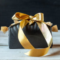 Black paper plate box with gold ribbon.