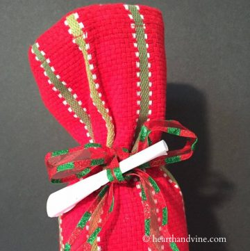 Wine bottle wrapped in red and green tea towel with a small paper scroll