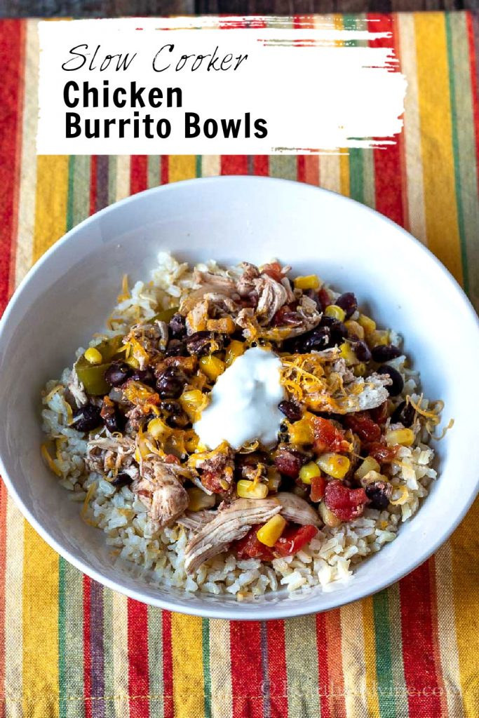 White bowl with chicken burrito mix on top of brown rice.