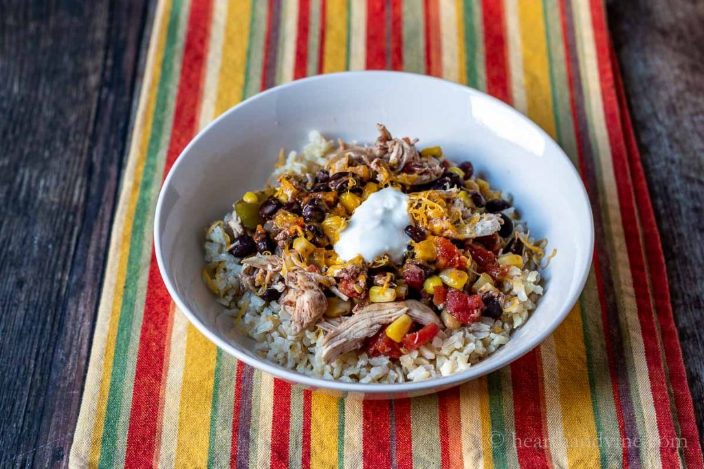 Slow cooker chicken burrito bowl with brown rice, cheddar cheese and sour cream.