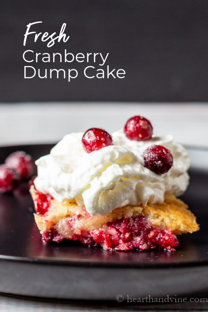 Serving of cranberry dump cake topped with whipped cream and sugared cranberries.