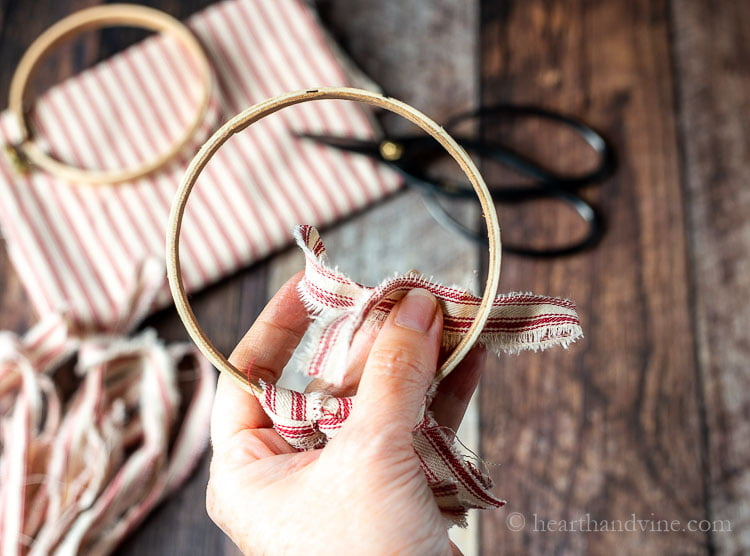Folded strip of red and white striped fabric set under an embroidery hoop edge.