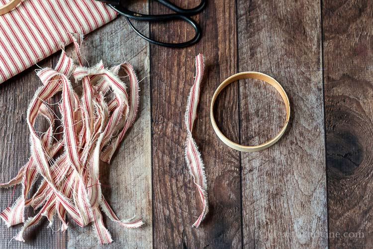 Small wooden embroidery hoop next to several strips of red and white fabric and a black pair of scissors.