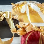 Three paper plate boxes with wrapped candies and gold bows.