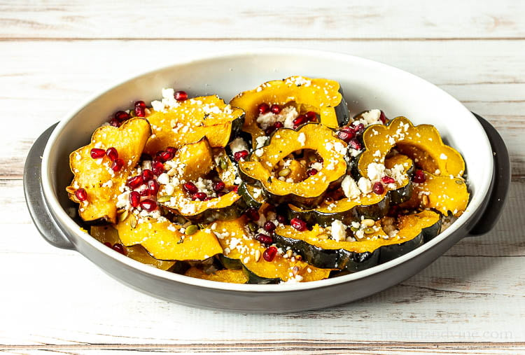 A serving dish with roasted acorn squash slices with pomegranate seeds, pine nuts, pepitos and queso fresco cheese.