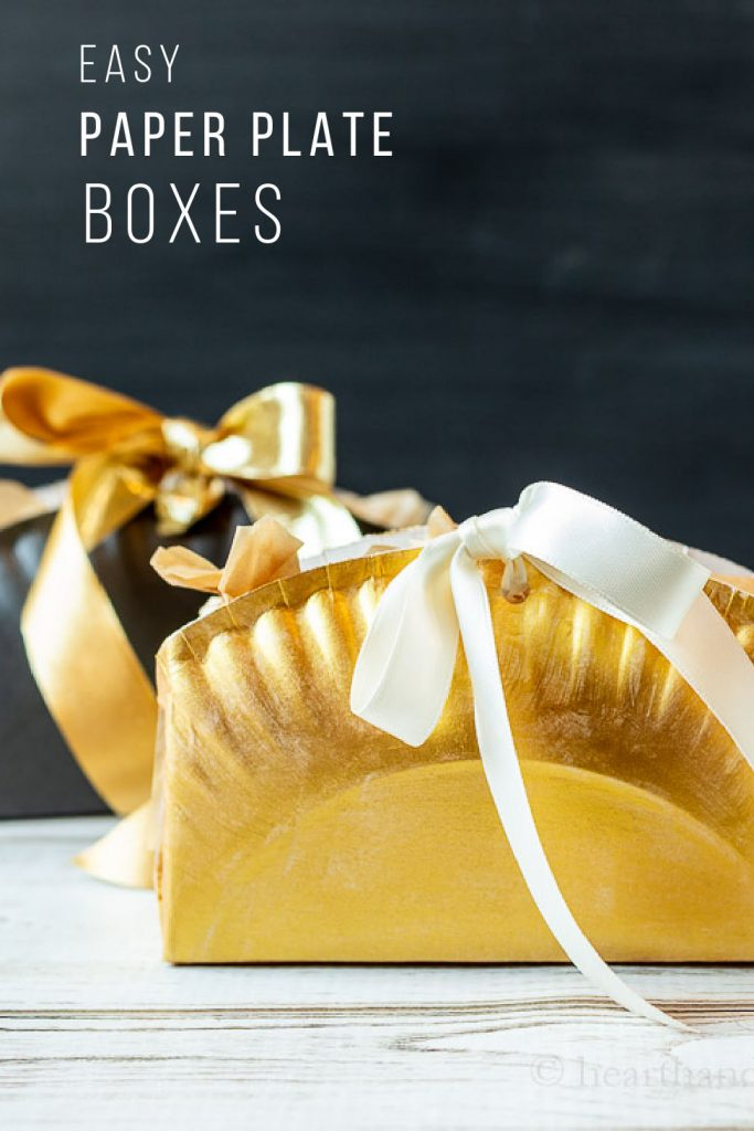 Gold and black paper plate boxes with gold and cream colored ribbons filled with candy.