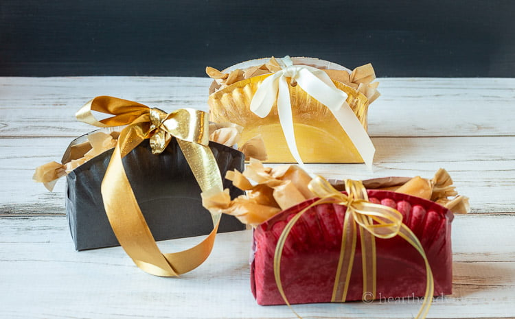 Three paper plate boxes. One black, one gold and one red. Each have wrapped candies inside and ribbons on the top.