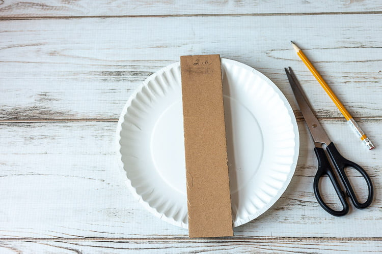 Paper plate with a strip of cardboard on top next to scissors and a pencil.