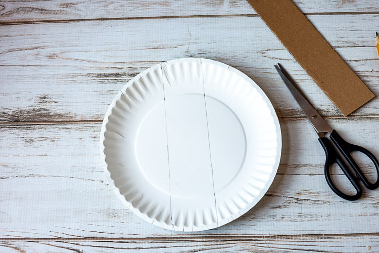 Paper plate with two lines down the middle, scissor and a 2 inch cardboard strip.
